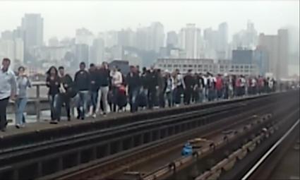 Usuários movimentam-se com trem na via